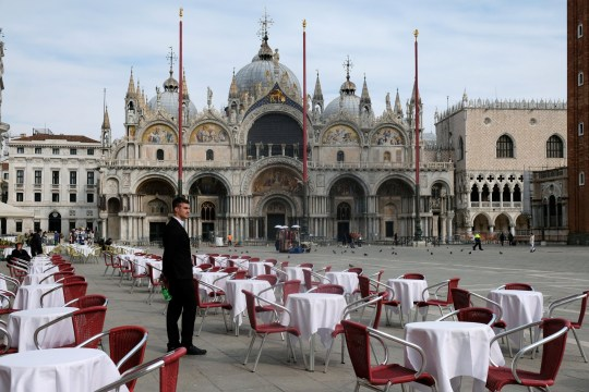 A waiter stands by empty tables outside a restaurant at St Mark's Square (Picture: Reuters)